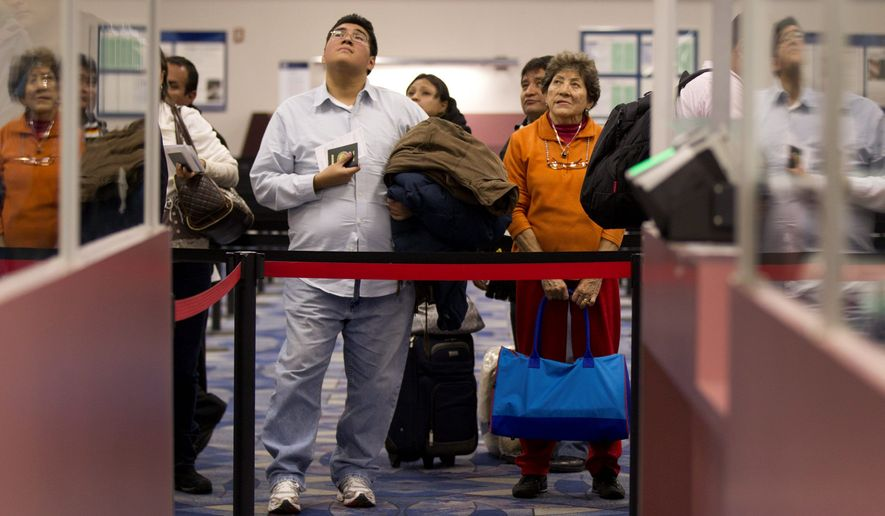 Non-resident visitors to the United States wait at the immigration control area after arriving at McCarran International Airport in Las Vegas on Dec. 13, 2011. (Associated Press) **FILE**