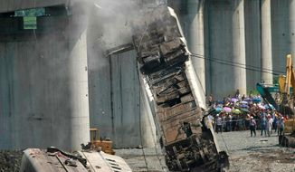 A derailed train car is removed from a bridge as workers clear up the wreckage after a train accident in Wenzhou in east China's Zhejiang province in July. A long-awaited government report said on Wednesday design flaws and sloppy management caused the bullet-train crash. (Associated Press)