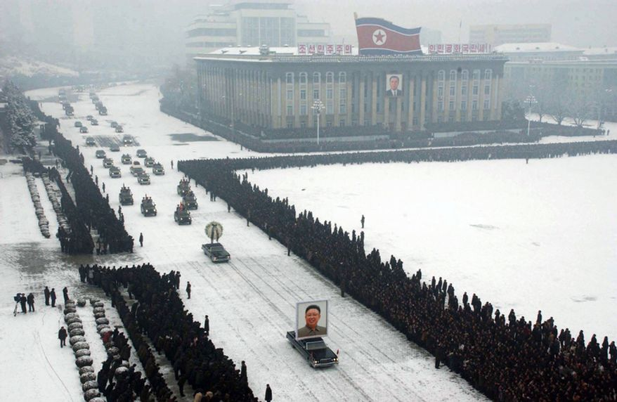 A portrait of late North Korean leader Kim Jong Il is carried past mourners during his funeral procession through the streets of Pyongyang, North Korea Wednesday Dec. 28, 2011.  (AP Photo/Kyodo News)