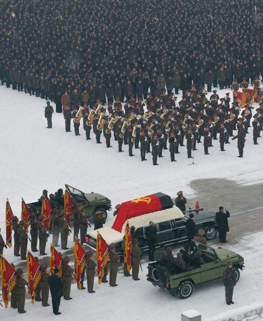 A hearse carrying the coffin of the late North Korean leader Kim Jong Il makes its way during his funeral procession.  (AP Photo/Kyodo News)