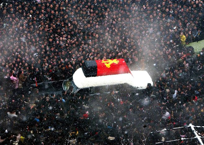 In this Wednesday, Dec. 28, 2011 photo released by the Korean Central News Agency and distributed in Tokyo, Dec. 29, 2011 by the Korea News Service, mourners surround the hearse carrying the coffin of the late North Korean leader Kim Jong Il during his funeral procession through the streets of Pyongyang, North Korea.  (AP Photo/Korean Central News Agency via Korea News Service)
