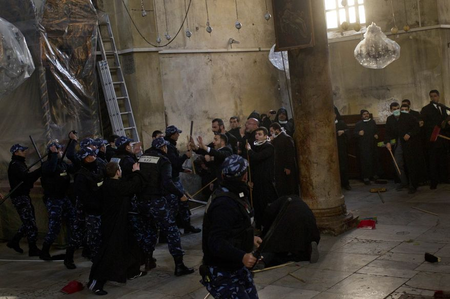 Palestinian police intervene in a fight between Greek Orthodox and Armenian clergymen during the cleaning of the Church of the Nativity in the West Bank town of Bethlehem on Wednesday, Dec. 28, 2011. (AP Photo/Bernat Armangue)