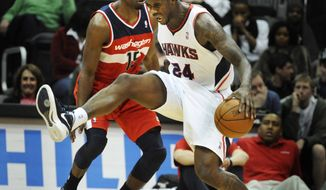 Atlanta Hawks forward Marvin Williams (24) is fouled by Washington Wizards guard Jordan Crawford (15) during the second half of an NBA game on Wednesday, Dec. 28, 2011, in Atlanta. Atlanta won 101-83. (AP Photo/John Amis)