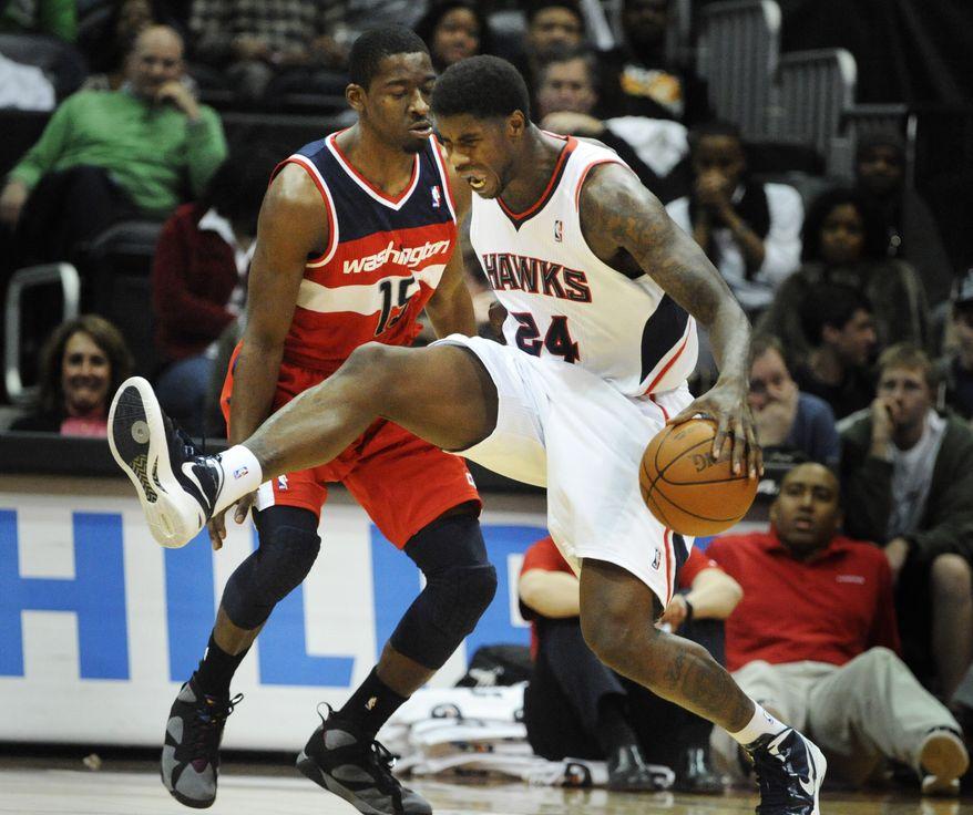 Atlanta Hawks forward Marvin Williams (24) is fouled by Washington Wizards guard Jordan Crawford (15) during the second half of an NBA game on Wednesday, Dec. 28, 2011, in Atlanta. Atlanta won 101-83. (AP Photo/John Amis)