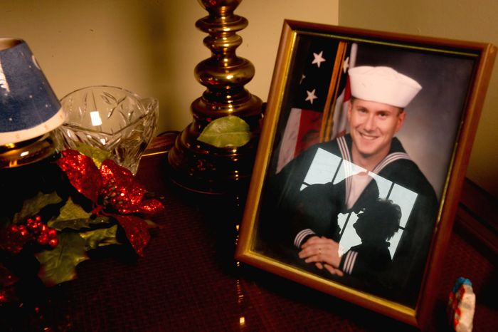 'CONNECTION': Bob and Carol Roddy are reflected in a portrait of son David, who died in Iraq in 2006. The Roddys have volunteered at BWI's USO lounge since 2008 as a way to ease the pain and stay busy. (Andrew Harnik/The Washington Times)