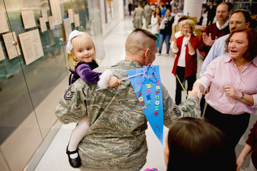 HOME AGAIN: Addison Reel, 2, of Dover, Del., is all smiles in the arms of her father, Air Force Tech Sgt. Scott Reel, upon his arrival at Baltimore-Washington International Thurgood Marshall Airport this month after a four-month deployment to Qatar. Operation Welcome Home Maryland was there to greet him. (Andrew Harnik/The Washington Times)