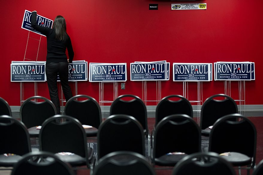 Alison Gibbs with the campaign sets up yard signs for supporters before Republican presidential candidate Ron Paul delivers a speech at a Jasper County town hall meeting held at the inner track of the Iowa Speedway, Newton, IA, Wednesday, December 28, 2011. (Andrew Harnik / The Washington Times)