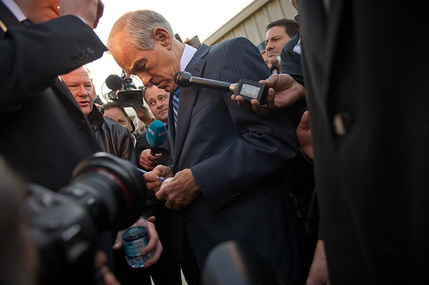 Republican presidential candidate Ron Paul signs a baseball after delivering a speech at a Jasper County town hall meeting held at the inner track of the Iowa Speedway, Newton, IA, Wednesday, December 28, 2011. (Andrew Harnik / The Washington Times)