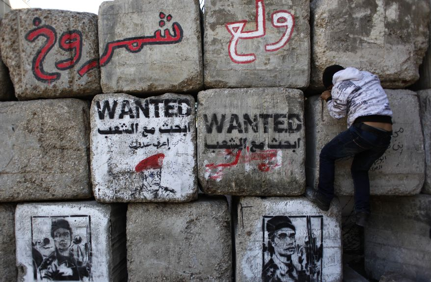 **FILE** An Egyptian child climbs cement blocks used to separate police forces from demonstrators Dec. 8, 2011, at the site of recent clashes in Cairo's Tahrir Square between police and demonstrators that left more than 40 people dead. The graffiti on the blocks depicts a police officer accused of targeting the eyes of protesters. (Associated Press)