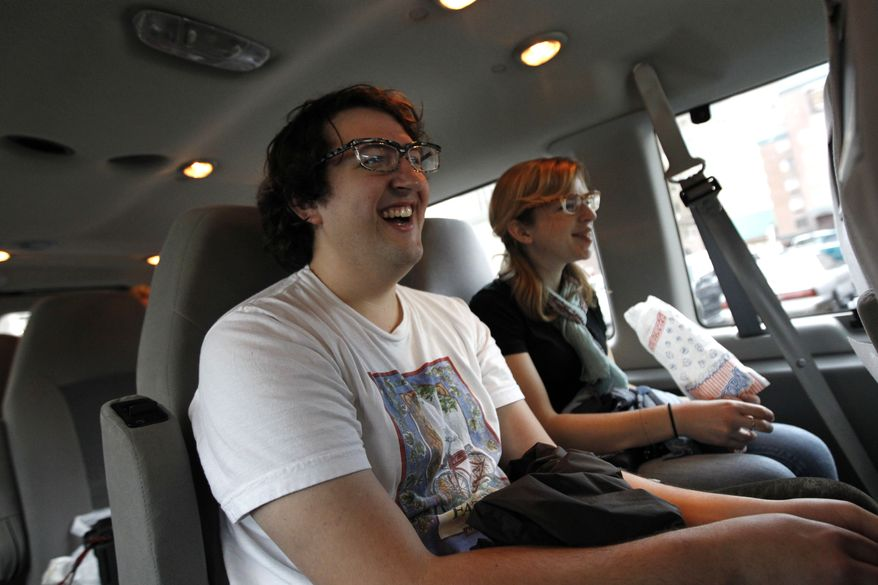 Adam Gertner, foreground, and Carly Myers laugh as they watch a movie clip during a movie tour in New Orleans. The tour, launched by New Orleans Movie Tours this summer, takes passengers to locations where famous movie scenes were filmed. The tour also includes peeks at the New Orleans homes of Brad Pitt, Sandra Bullock and John Goodman. (AP Photo/Gerald Herbert)