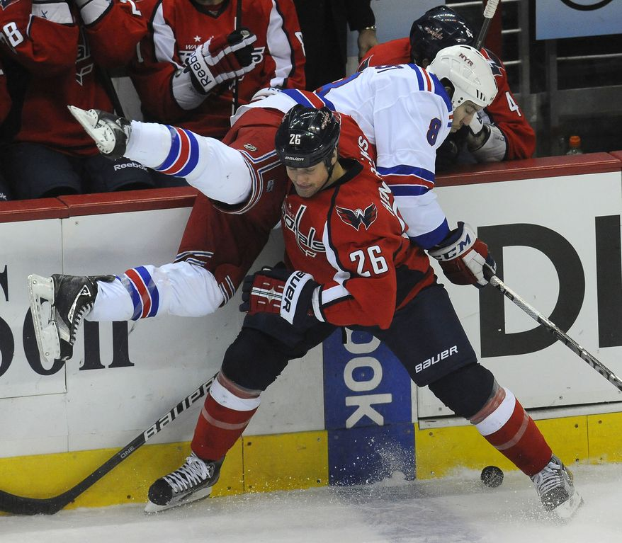 Washington Capitals' Matt Hendricks lifts New York Rangers' Brandon Prust off the ice and away from the puck during the first period Wednesday, Dec. 28, 2011, in Washington. (AP Photo/Richard Lipski)