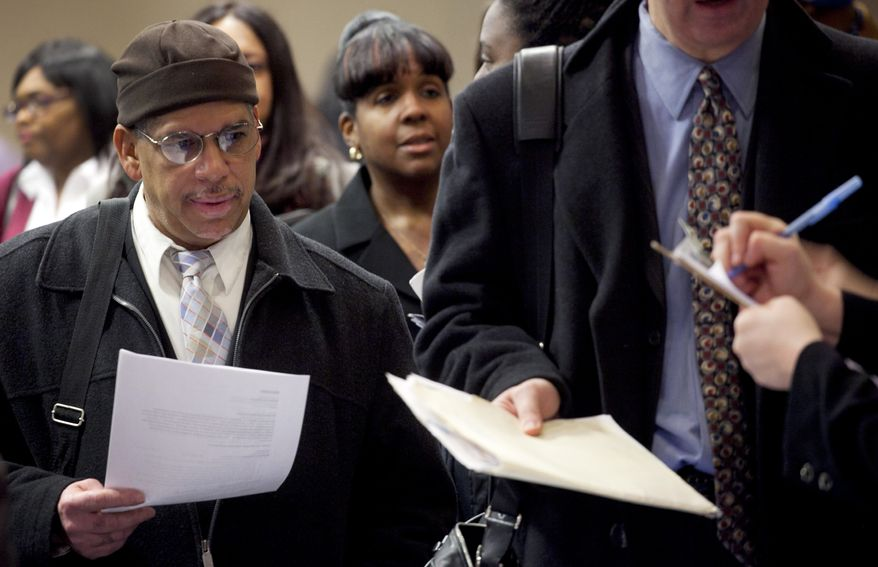 **FILE** People wait to talk with potential employers Dec. 12, 2011, at a job fair in New York sponsored by National Career Fairs. (Associated Press)