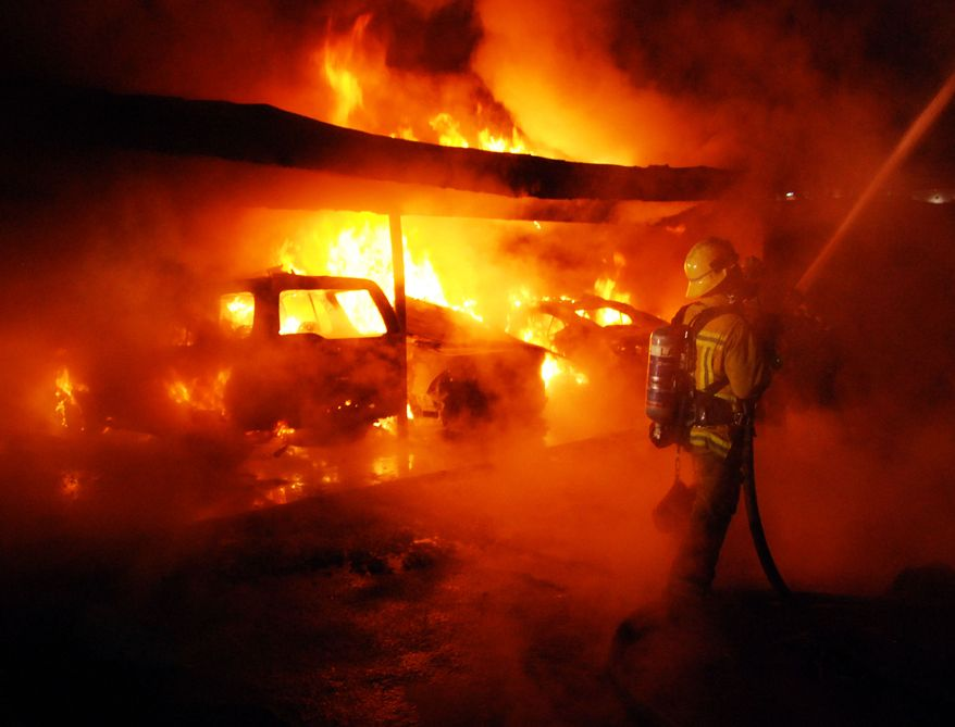 A Los Angeles Fire Department firefighter is shown Dec. 30, 2011, at a fire in West Hollywood, Calif. An arsonist torched car after car earlier in the day, sending firefighters scrambling to put out more than a dozen blazes in Hollywood and neighboring West Hollywood. (Associated Press)