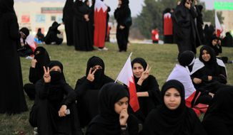 Bahraini anti-government protesters wear and hold national flags Dec. 30, 2011, during a sit-in near Abu Saiba, Bahrain, in the center of a traffic circle on a highway that runs past several Shiite Muslim villages. (Associated Press)