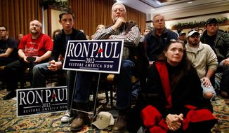 Supporters listen as Rep. Ron Paul of Texas speaks at a campaign event at the Hotel Pattee in Perry, Iowa, on Thursday. All of the Republicans are fielding questions about cutting spending and whether they are the candidate who can do it. (Associated Press)