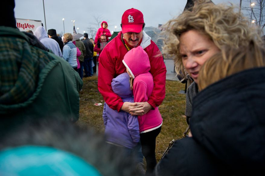 Eric Liskey of West Des Moines, Iowa, huddles for warmth with his daughters, 7 year old Claire, left, and 10 year old Katie while they wait for republican presidential candidate Mitt Romney to arrive for a cold, rainy, early morning rally at a Hy-Vee grocery store, West Des Moines, IA, Friday, December 30, 2011. (Andrew Harnik / The Washington Times)