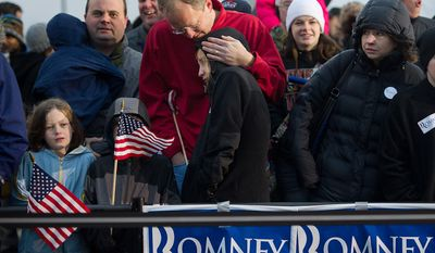 Chris Jenkins of West Des Moines, Iowa, center, comforts his cold 12 year old daughter Lauren while they wait for republican presidential candidate Mitt Romney to arrive for a cold, rainy, early morning rally at a Hy-Vee grocery store, West Des Moines, IA, Friday, December 30, 2011. (Andrew Harnik / The Washington Times)