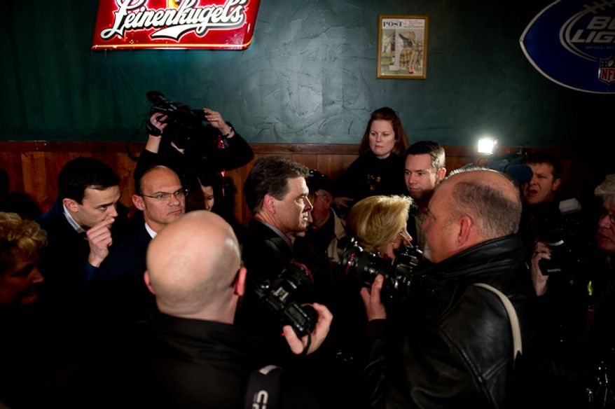 Republican presidential candidate Rick Perry makes his way through the crowd after speaking at the Fainting Goat Restaurant, Waverly, IA, Friday, December 30, 2011. (Andrew Harnik / The Washington Times)