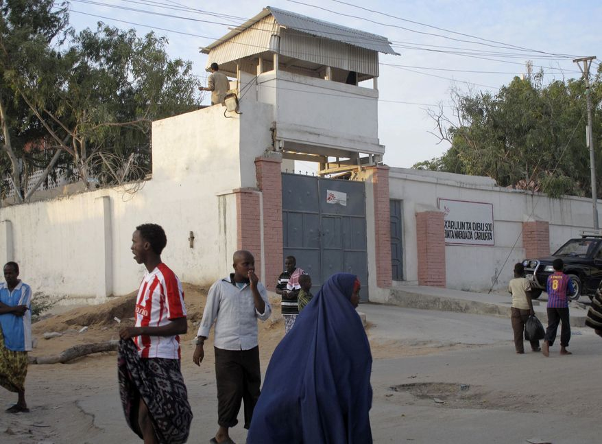 Residents walk outside of the compound of aid group Medecins Sans Frontieres (Doctors without Borders) in Mogadishu, Somalia, on Dec. 29, 2011. A disgruntled former employee shot at least two international workers from the group at the group's office earlier that day, a security guard said. (Associated Press)