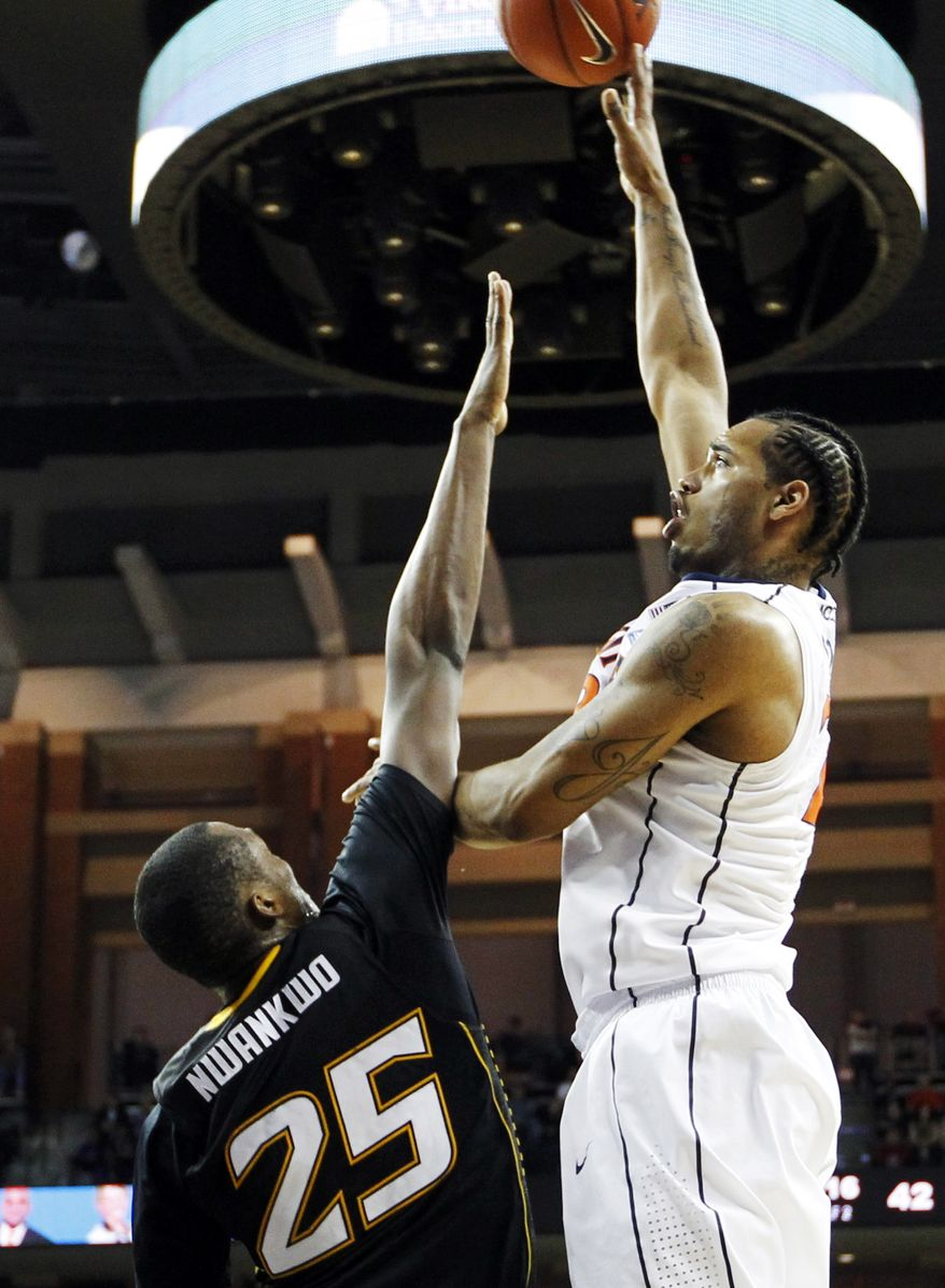 Virginia forward Mike Scott (23) shoots over Towson forward Robert Nwankwo (25) during a game, Friday, Dec. 30, 2011, in Charlottesville, Va. Virginia won 57-50, though Scott was limited to just seven points. (AP Photo/The Daily Progress, Sabrina Schaeffer)