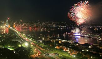 Fireworks burst over the Sydney Opera House, right, as New Year's celebrations begin in Sydney, Saturday, Dec. 31, 2011. (AP Photo/Rick Rycroft)