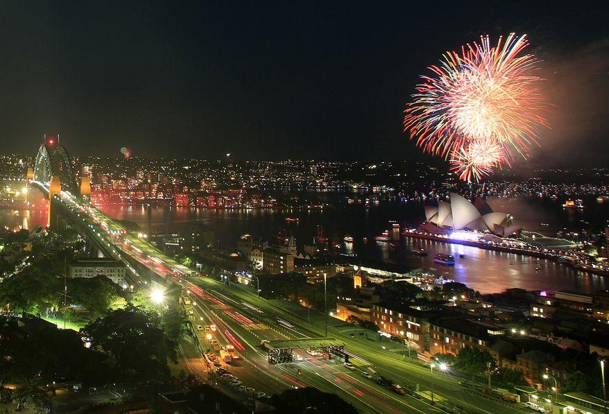 Fireworks burst over the Sydney Opera House, right, as New Year's celebrations begin in Sydney, Saturday, Dec. 31, 2011. (AP Photo/Rick Rycroft)