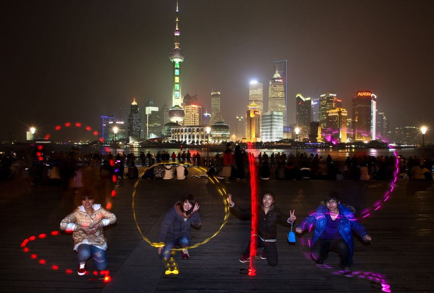 IME EXPOSURE WITH LIGHT PAINTING - In this Saturday, Dec. 31, 2011 photo, Chinese use lights to draw a 2012 sign at a bund as they celebrate New Year in Shanghai, China. (AP Photo) CHINA OUT