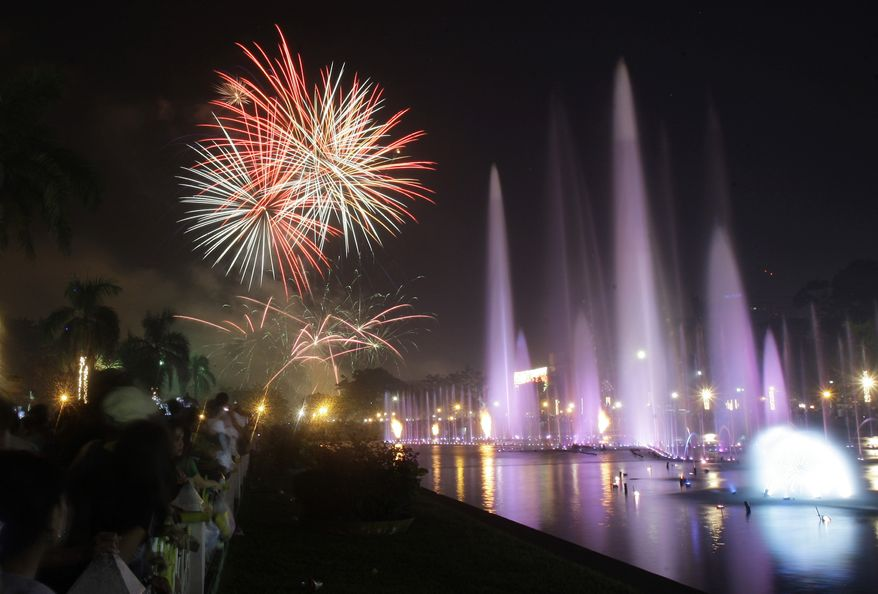 Filipinos watch a fireworks and water fountain display as they welcome the New Year at Manila's Rizal Park, Philippines on Sunday Jan. 1, 2012. More than 200 people have been injured by illegal firecrackers and celebratory gunfire in the Philippines despite a government scare campaign against reckless New Year revelries, officials recently said. (AP Photo/Aaron Favila)