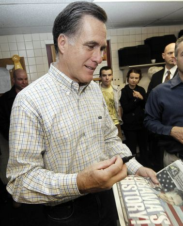 """Republican presidential candidate, former Massachusetts Gov. Mitt Romney prepares to sign a newspaper with the headline """"Obama's History!"""" during a campaign stop at Old Salt Restaurant in Hampton, N.H. Dec. 31, 2011. (AP Photo/Winslow Townson)"""