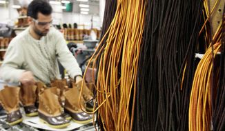 Amer Saleh, of Westbrook, Maine, places shoelaces on pairs of boots in the facility where L.L. Bean boots are assembled in Brunswick, Maine. L.L. Bean's famed hunting boots are seeing a surge in popularity, necessitating the hiring of more than 100 additional employees to make them. (Associated Press)
