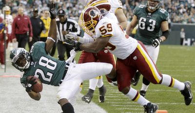 Philadelphia Eagles' Dion Lewis (28) is knocked out of bounds near the goal line by Washington Redskins' London Fletcher (59) and Oshiomogho Atogwe (20) during the second half of an NFL football game, Sunday, Jan. 1, 2012, in Philadelphia. (AP Photo/Mel Evans)