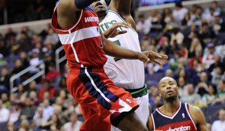 Washington Wizards guard John Wall goes to the basket against Boston Celtics center Jermaine O'Neal during the second half, Sunday, Jan. 1, 2012, in Washington. The Celtics won 94-86. (AP Photo/Nick Wass)