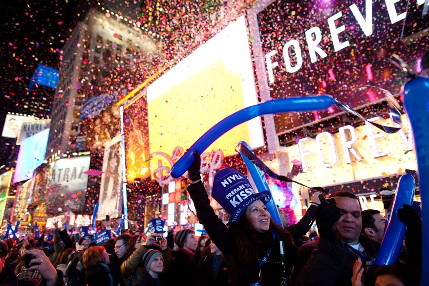 """Revelers cheer at midnight in Times Square on New Years Eve, Saturday, Dec. 31, 2011, in New York. Some revelers, wearing party hats and """"2012"""" glasses, began camping out Saturday morning, as workers readied bags stuffed with hundreds of balloons and technicians put colored filters on klieg lights. (AP Photo/John Minchillo)"""