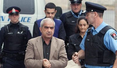Mohammad Shafia (front left), son Hamed Shafia (background, second from left), and wife Tooba Mohammad Yahya (behind officer on right) arrive at the Frontenac County Courthouse in Kingston, Canada. Authorities accuse the three of killing the three daughters in the Afghan immigrant family because they dishonored it by adopting such habits as dating and wearing revealing clothes. (Canadian Press via Associated Press)