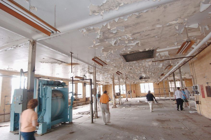 A photograph from June 2007 shows the condition of Weston Hospital before Joe Jordan, and asbestos-removal and demolition contractor, bought it at auction. His family has turned it into a museum hosting year-round paranormal tours and ghost hunts. His daughter Rebecca Jordan shows off an exhibit in the museum. (Associated Press) **FILE**
