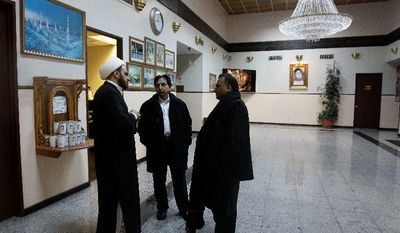 Imam Maan Al-Sahlani (left) speaks with Syed Raza and Javaid Hussain in the lobby of the Iman Al-Khoei Islamic Center in New York on Monday, a day after someone hurled a Molotov cocktail at the building's facade. Police are also investigating similar attacks on a nearby bodega and two houses as possible bias crimes. (Associated Press)