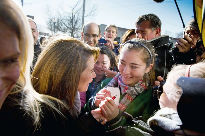 After a campaign stop at Paula's Maid Rite Restaurant in West Des Moines, Iowa, on Monday, Michele Bachmann greets Advanced Placement government and history students from Taylor High School of Cincinnati, Ohio. Mrs. Bachmann's husband, Marcus, is at right. (Andrew Harnik/The Washington Times)