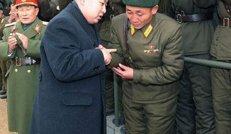 "TIES THAT BIND: North Korea's ""supreme leader,"" Kim Jong-un, speaks with a soldier on New Year's Day during his inspection of a tank division to congratulate members of the Korean People's Army. (Korean Central News Agency via Associated Press)"