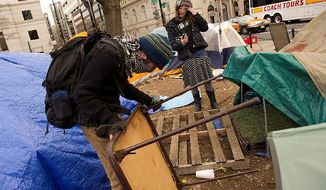 "A protester who calls himself ""Harmony"" helps Lexi Ricciardelli, of New Jersey, add a folding table that will serve as an entranceway to her tent. (Barbara L. Salisbury/The Washington Times)"