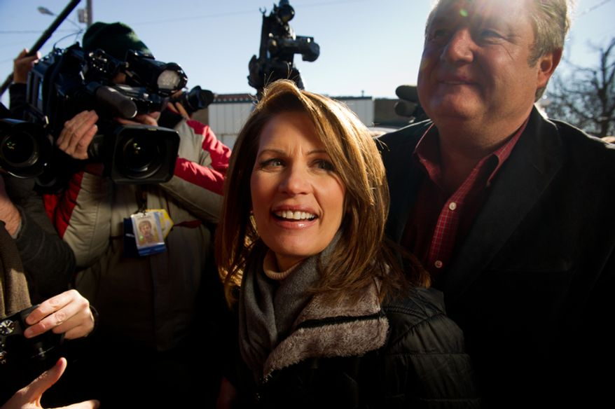 Republican presidential candidate Michele Bachmann along side her husband, Marcus, right, greets people after visiting Paula's Maid Rite Restaurant on a campaign stop. (Andrew Harnik / The Washington Times)
