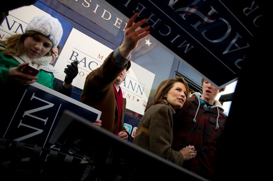 Republican presidential candidate Michele Bachmann autographs campaign signs for Juniors and seniors from Taylor High School in Cincinnati, Ohio during a campaign stop. (Andrew Harnik / The Washington Times)