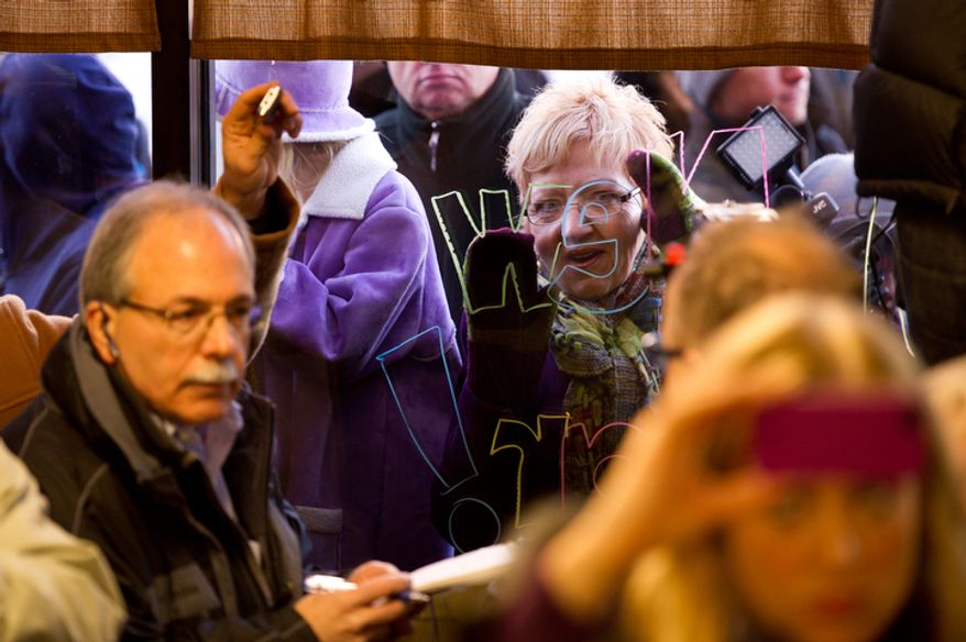 A woman peeks in the window to try to see Republican presidential candidate Rick Santorum as he delivers a standing room only speech at a campaign stop at The Reising Sun Cafe, Polk City, IA, Monday, January 2, 2012. (Andrew Harnik / The Washington Times)