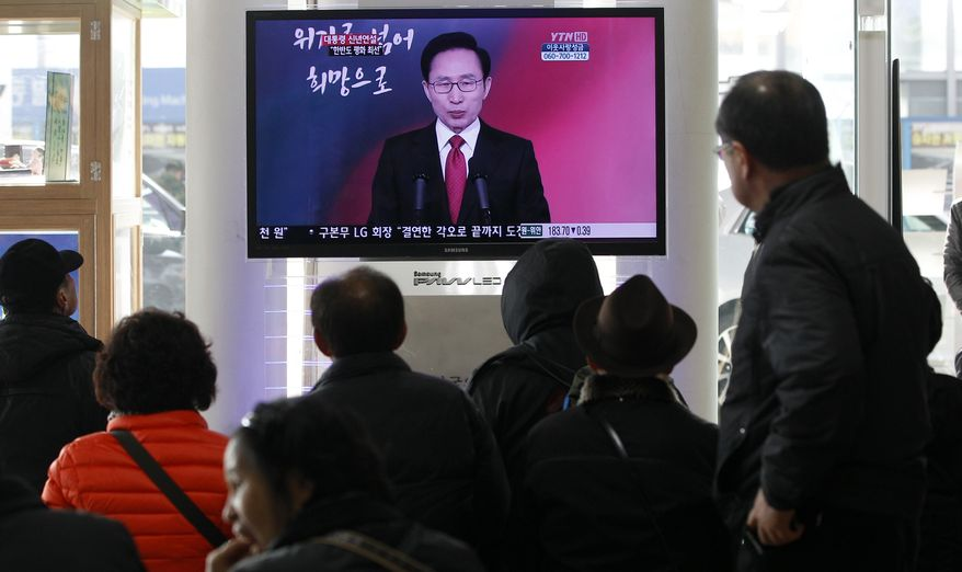 People at the Seoul Station on Jan. 2, 2012, watch a TV screen showing South Korean President Lee Myung-bak delivering a New Year's speech to the nation. (Associated Press)