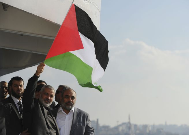 Gazan Prime Minister Ismail Haniyeh waves a Palestinian flag from the Mavi Marmara ship he visited in Istanbul on Jan. 2, 2012. The ship was the target of a deadly raid by Israeli troops seeking to prevent an aid flotilla from reaching the Palestinian territory. (Associated Press)
