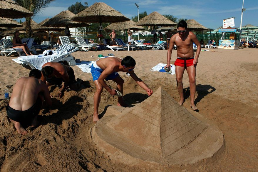 Tourists build a sand pyramid at a closed beach at the Red Sea resort of Sharm el-Sheik, Egypt. Some Islamists have a message for foreign tourists: Welcome to Egypt, but no booze, bikinis or mixed bathing at beaches. But if such strictures were imposed, it could hurt the tourism industry. (Associated Press)