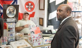 ASSOCIATED PRESS The Rev. David Kennedy checks out items for sale at the Redneck Shop in Laurens, S.C., as proprietor John Howard looks on, in February 2008. A judge has ruled that Mr. Kennedy's New Beginnings Baptist Church is the rightful owner of the building where the shop is located.