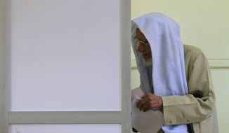 ** FILE ** An Egyptian man votes on Tuesday, Jan. 3, 2012, at a polling center in Qalyobeia, Egypt, during the third round of the country's first parliamentary elections following the ouster of President Hosni Mubarak. (Associated Press)