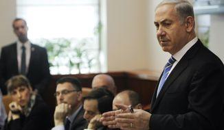 Israeli Prime Minister Benjamin Netanyahu (right) speaks Jan. 1, 2012, during the weekly cabinet meeting in Jerusalem. (Associated Press)