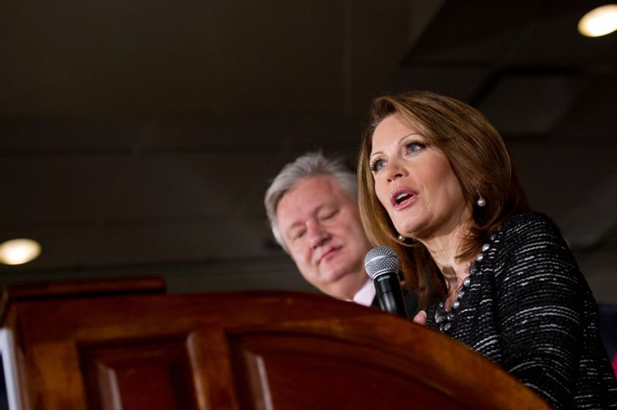 Rep. Michele Bachmann, with her husband, Marcus, announces in West Des Moines, Iowa, on Wednesday, Jan. 4, 2012, that she will end her Republican presidential campaign after finishing sixth in Tuesday's Iowa Republican caucuses. (Andrew Harnik/The Washington Times)