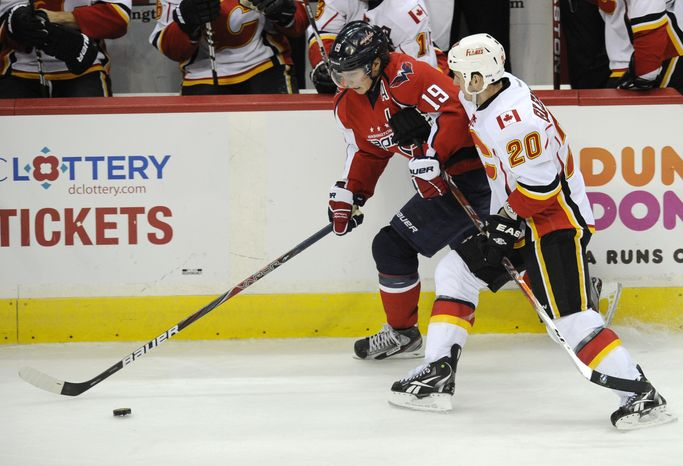 Calgary Flames left wing Curtis Glencross (20) battles for the puck against Washington Capitals center Nicklas Backstrom on Jan. 3, 2012, during the third period of the Capitals' 3-1 victory in Washington. (Associated Press)